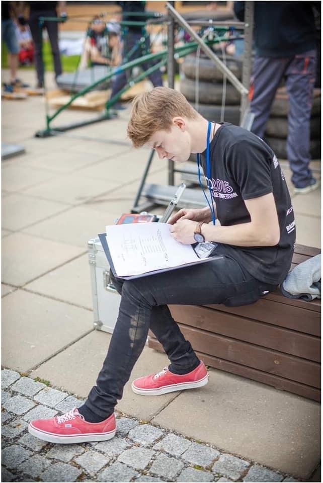Martin Pärnak sitting on bench, reading.